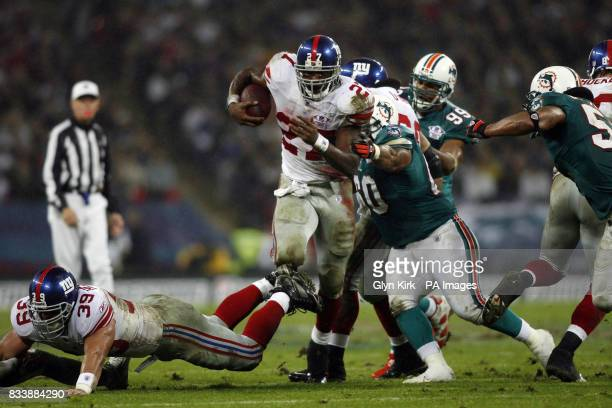 New York Giants No27 Brandon Jacobs is tackled by Miami Dolphins' Steve Fifita during the NFC Eastern Division match at Wembley London