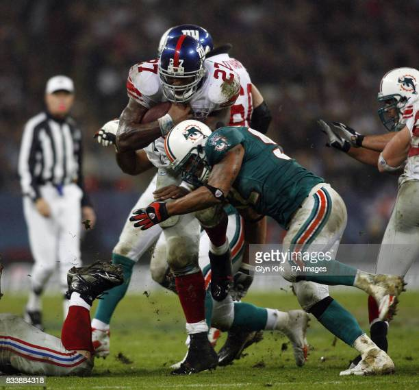 New York Giants No27 Brandon Jacobs is tackled by Miami Dolphins Steve Fifita during the NFC Eastern Division match at Wembley London