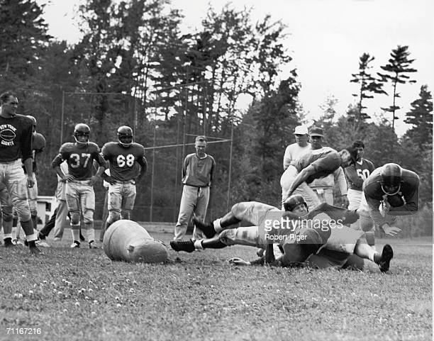 New York Giants participate in a practice or training camp as offensive coordinator Vince Lombardi at right in hat looks on late 1950s Coowner and...