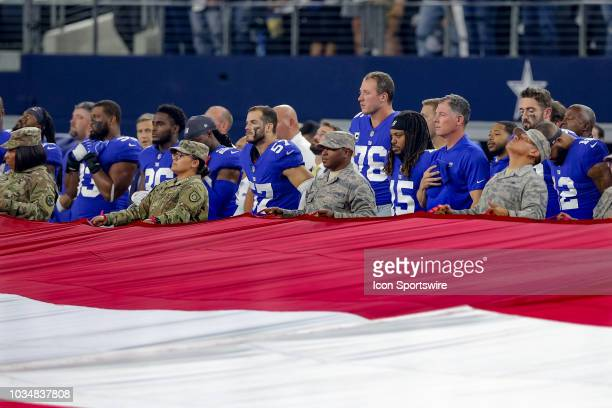 New York Giants players and coaches stand with military members for the playing of the National Anthem prior to the game between the New York Giants...