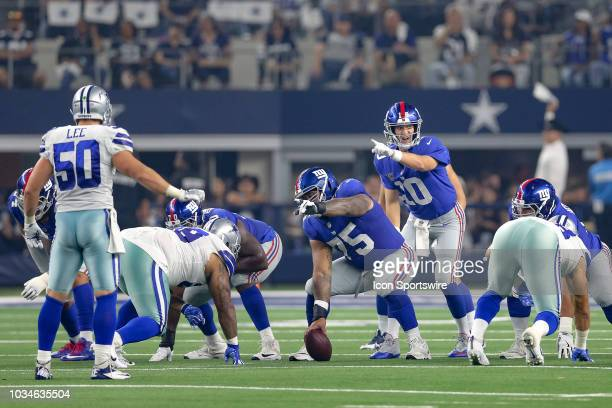 New York Giants quarterback Eli Manning and center Jon Halapio point out the blocking assignments at the line of scrimmage during the game between...