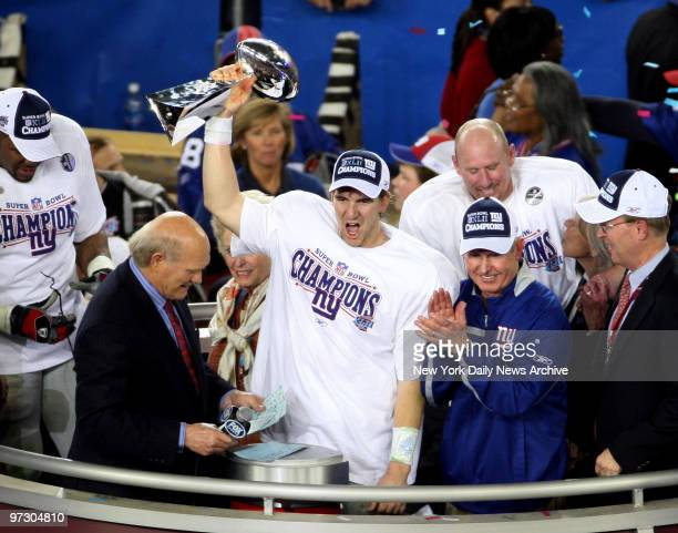 New York Giants' quarterback Eli Manning holds up the Vince Lombardi trophy as he stands next to head coach Tom Coughlin after the Giants pulled off...