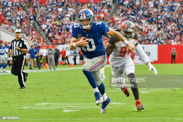 New York Giants quarterback Eli Manning is pursued by Tampa Bay Buccaneers defensive lineman Will Clarke as he scrambles for a touchdown during an...