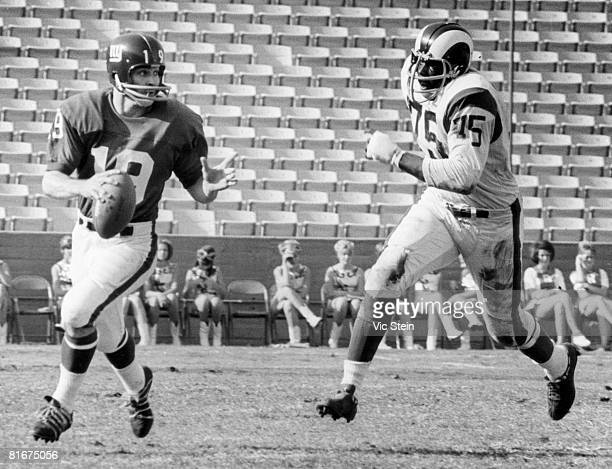 New York Giants quarterback Gary Wood is chased from the pocket by Los Angeles Rams defensive end Deacon Jones inducted into the Pro Football Hall of...