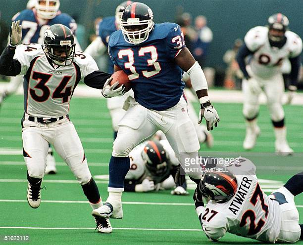 New York Giants running back Gary Brown shakes off tackles by Denver Broncos players Tyrone Braxton and Steve Atwater en route to a 45yard gain in...