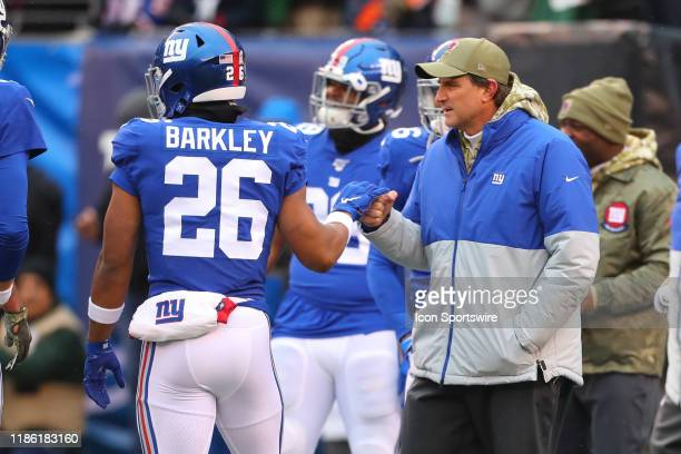 New York Giants running back Saquon Barkley high fives New York Giants Offensive Coordinator Mike Shula prior to the National Football League game...