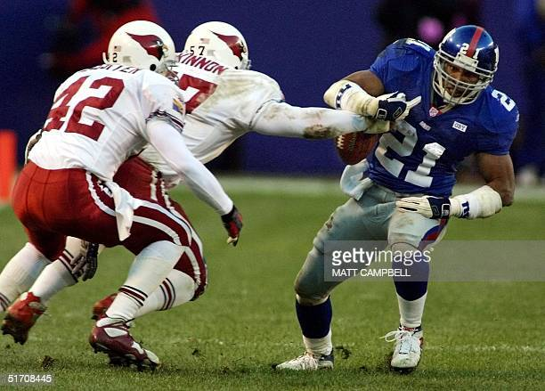 New York Giants running back Tiki Barber has the ball stripped from his hands by Arizona Cardinal lnebacker Ronald McKinnon as safety Kwame Lassiter...