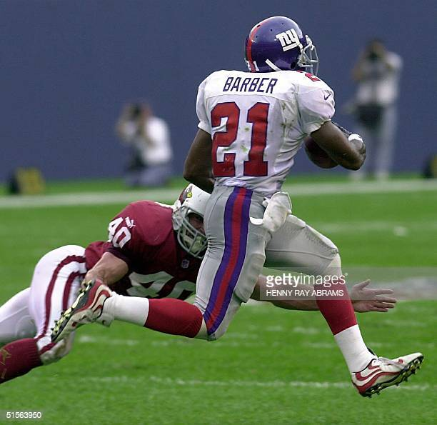 New York Giants' Tiki Barber evades the grasp of the Arizona Cardinals' Pat Tillman to run for a 78yard touchdown in the second quarter of their game...