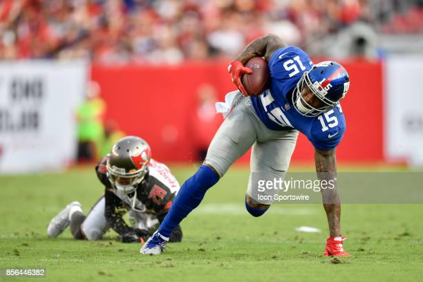 New York Giants wide receiver Brandon Marshall can't quite keep his balance after stepping through a tackle during an NFL football game between the...