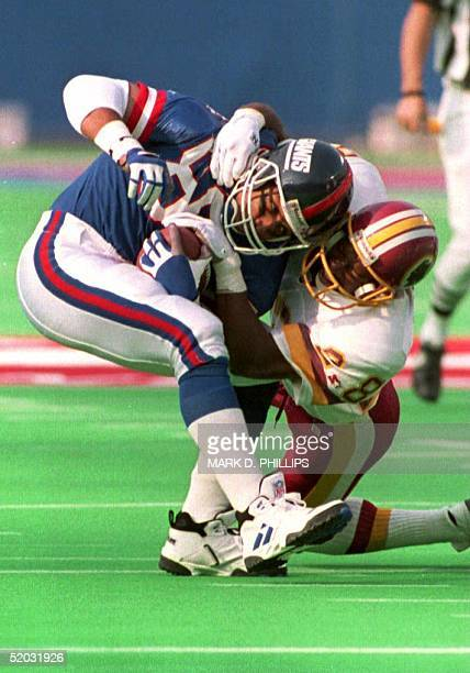 New York Giants wide receiver Chris Calloway tries to slip from the grasp of Washington Redskins cornerback Darrell Green after making a rception in...