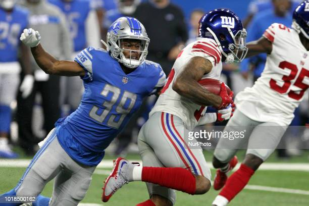 New York Giants wide receiver Hunter Sharp runs the ball under the pressure of Detroit Lions cornerback Jamal Agnew during the first half of an NFL...