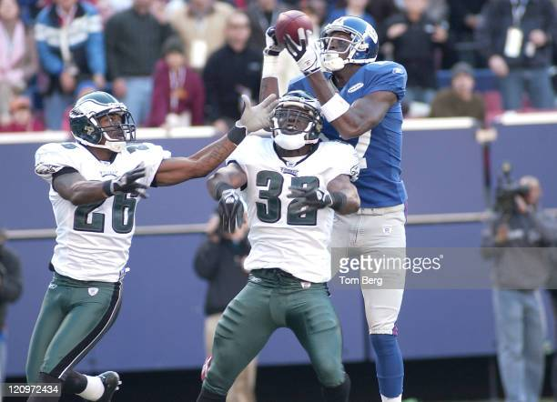 New York Giants Wide Receiver Plaxico Burress catching a pass while Eagles Safety Michael Lewis and Eagles Cornerback Lito Sheppard defend during...