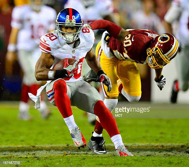New York Giants wide receiver Victor Cruz picks up yardage after a catch against Washington Redskins defensive back Cedric Griffin in the second...