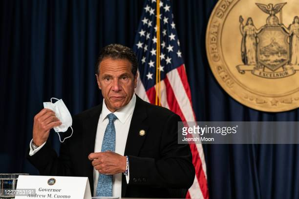 New York Gov. Andrew Cuomo takes off a protective mask during the daily media briefing at the Office of the Governor of the State of New York on July...