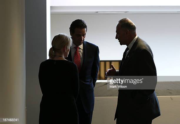 New York Gov Andrew Cuomo talks with US Sen Kirsten Gillibrand and US Sen Chuck Schumer while visiting Capitol Hill on December 3 2012 in Washington...