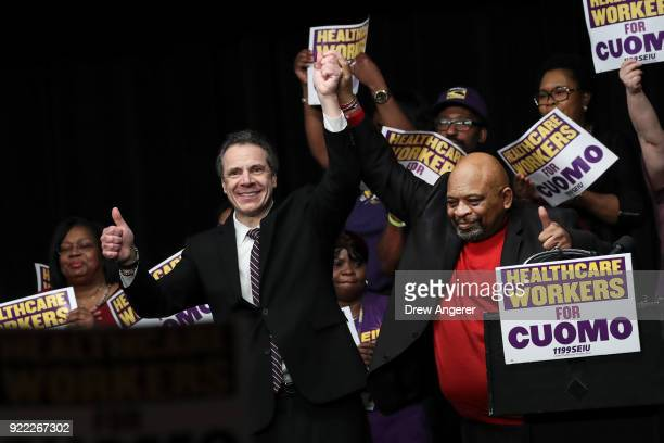 New York Governor Andrew Cuomo and 1199SEIU United Healthcare Workers East President George Gresham gesture to the crowd at a healthcare union rally...