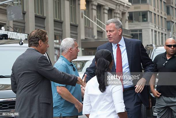 New York Governor Andrew Cuomo and New York City Mayor Bill de Blasio shake hands as they arrive at the scene of an explosion on West 23rd Street...