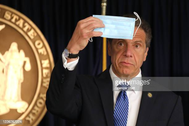 New York Governor Andrew Cuomo holds up a face mask at a news conference on May 21, 2020 in New York City. While the governor continued to say that...