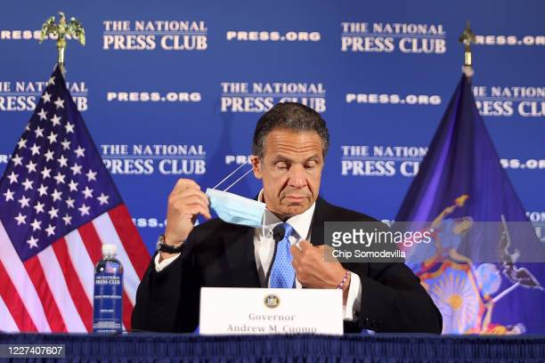 New York Governor Andrew Cuomo removes his face mask at the start of a news conference at the National Press Club May 27, 2020 in Washington, DC....