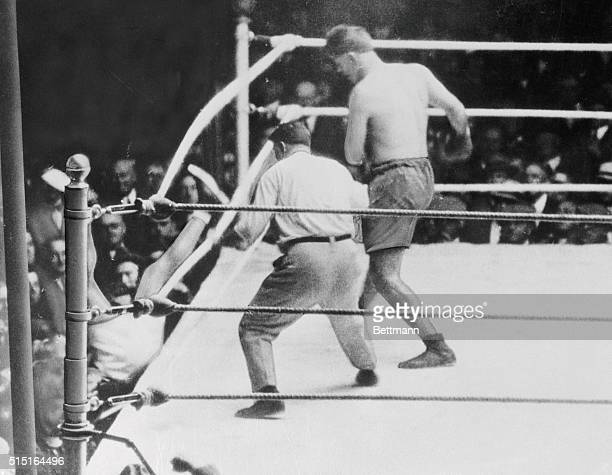 New York: Heavyweight champ Jack Dempsey falls out of the ring after being driven through the ropes by Argentina's Luis Firpo in the first round of...