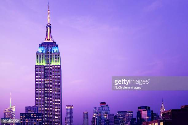 new york high rise buildings at night. empire state building in foreground - empire state building stock pictures, royalty-free photos & images