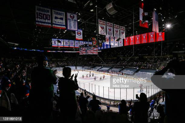 New York Islanders and the Philadelphia Flyers stand during the National Anthem at Nassau Coliseum on March 18, 2021 in Uniondale, New York....