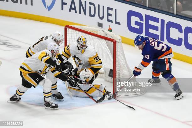 New York Islanders center Casey Cizikas attempts a wrap around goal but is stopped by the efforts of Pittsburgh Penguins goaltender Matt Murray...