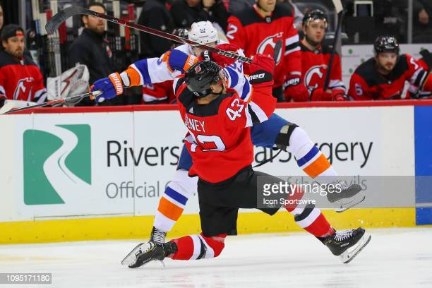 New York Islanders center Casey Cizikas hits New Jersey Devils left wing Brett Seney during the first period of the National Hockey League game...