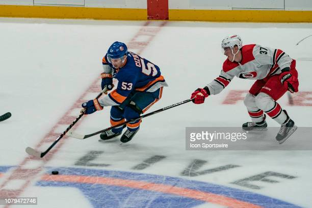 New York Islanders Center Casey Cizikas skates with the puck with Carolina Hurricanes Right Wing Andrei Svechnikov defending during the second period...