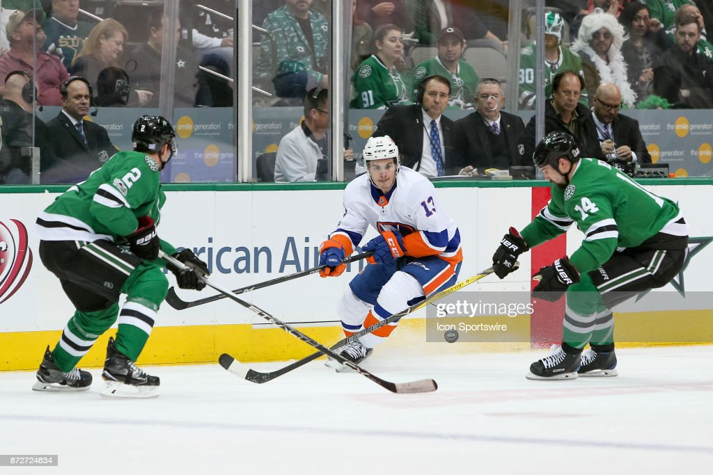 New York Islanders Center Mathew Barzal (13) plays a puck between Dallas Stars Left Wing Jamie Benn (14) and Defenceman Dan Hamhuis (2) during the NHL hockey game between the New York Islanders and Dallas Stars on November 10, 2017 at American Airlines Center in Dallas, TX.