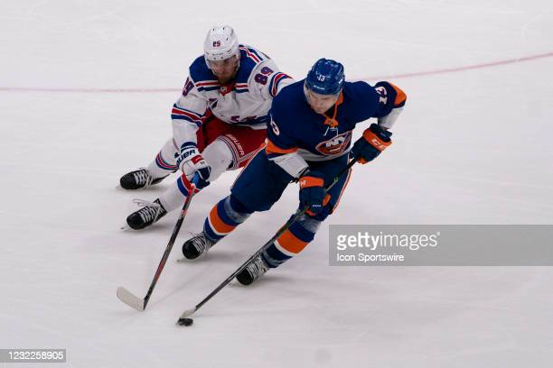 New York Islanders Center Mathew Barzal skates with the puck with New York Rangers Right Wing Pavel Buchnevich in pursuit during the second period of...
