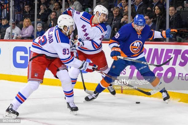 New York Islanders Defenceman Adam Pelech New York Rangers Center Mika Zibanejad and New York Rangers Left Wing Chris Kreider battle on the boards...