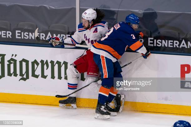 New York Islanders Defenseman Adam Pelech checks New York Rangers Center Mika Zibanejad into the boards during the first period of the National...
