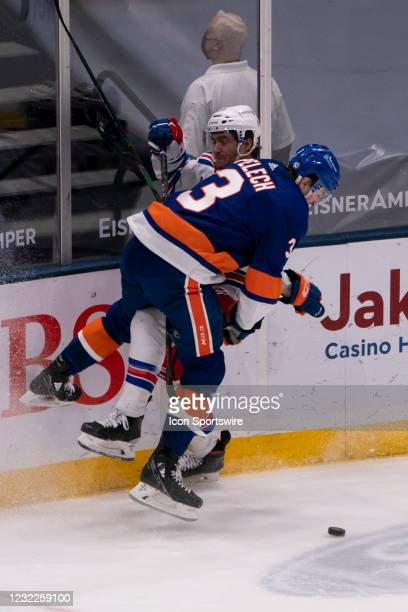 New York Islanders Defenseman Adam Pelech checks New York Rangers Center Kevin Rooney into the boards during the third period of the National Hockey...