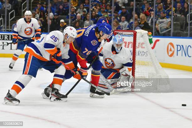 New York Islanders defenseman Devon Toews and St Louis Blues center Oskar Sundquist go after a loose puck during an NHL game between the New York...
