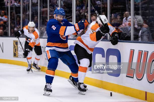 New York Islanders Defenseman Nick Leddy puts a hit on Philadelphia Flyers Forward Cole Bardreau with Taylor Leier watching the play develop during a...
