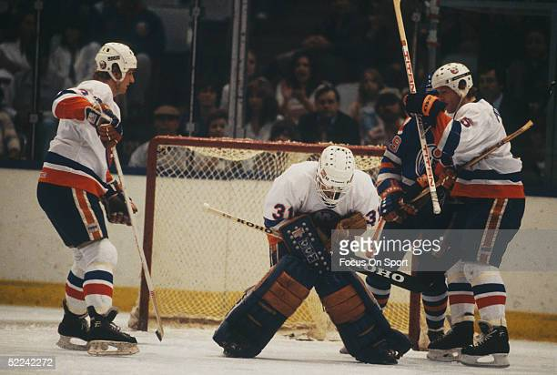 New York Islanders' goalie Billy Smith crouches over a save against the Minnesota North Stars during a game at the Nassau Coliseum circa 1984 in...