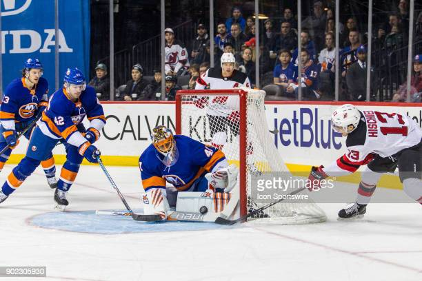 New York Islanders Goalie Jaroslav Halak makes a save as New Jersey Devils Center Nico Hischier tries to wrap the puck around the net during the...