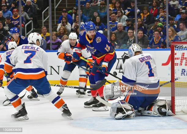 New York Islanders goaltender Thomas Greiss blocks a shot by St Louis Blues leftwing Zach Sanford during an NHL game between the New York Islanders...