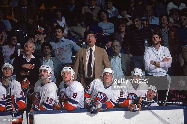 New York Islanders head coach Al Arbour and players watch a game from the bench at Nassau Coliseum Uniondale Long Island New York March 1985 The...