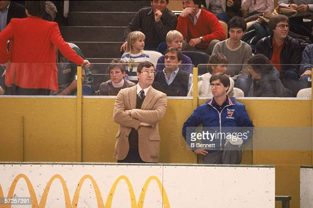 New York Islanders' head coach Al Arbour and trainer Ron Waske watch a road game from the bench 1980s