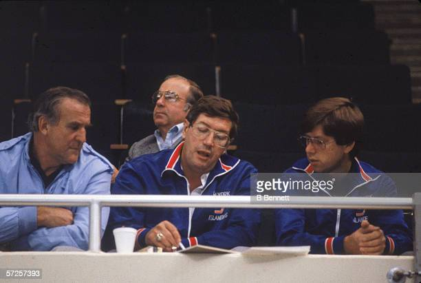 New York Islanders head coach Al Arbour talks to Islanders trainer Ron Waske as an unidentified man listens October 1983