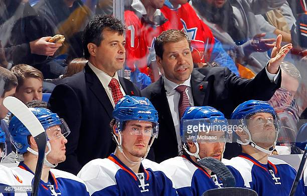 New York Islanders Head coach Jack Capuano talks to Assistant Coach Doug Weight on the bench during the game against the Colorado Avalanche on...