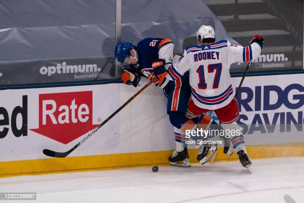 New York Islanders Left Wing Michael Dal Colle is checked into the boards by New York Rangers Center Kevin Rooney during the third period of the...