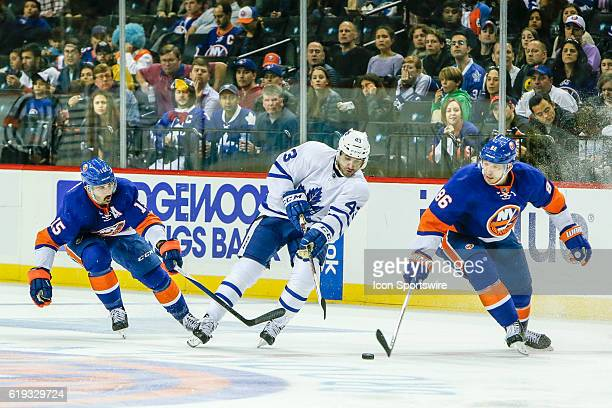 New York Islanders Right Wing Cal Clutterbuck Toronto Maple Leafs Center Nazem Kadri and New York Islanders Winger Nikolay Kulemin fight for puck...