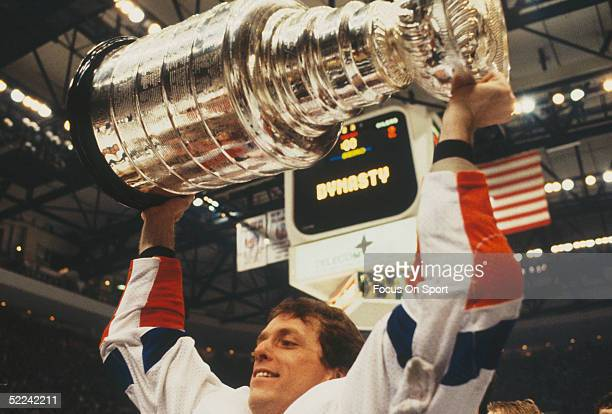 New York Islanders' Wayne Merrick hoists the Stanley Cup over his head after the Islander's victory over the Vancouver Canucks at the Nassau Coliseum...