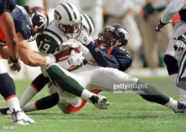 New York Jet Keyshawn Johnson is tackled by Denver Bronco Tyrone Braxton and Bill Romanowski during their 03 October, 1999 game at Mile High Stadium...