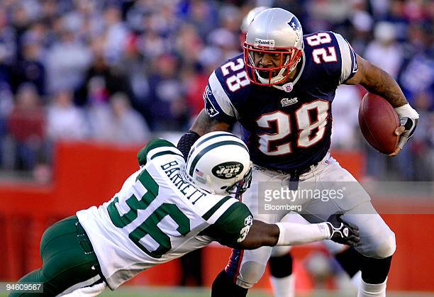 New York Jets cornerback David Barrett left tackles New England Patriots running back Corey Dillon during the first quarter of their AFC wild card...