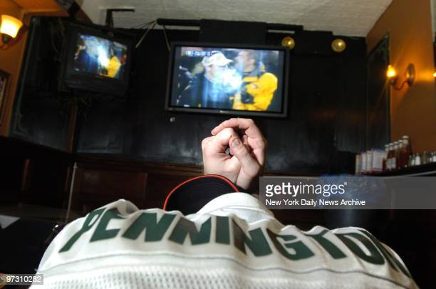 New York Jets' fan wearing a Chad Pennington jersey strikes a prayerful pose in front of a television set as the Jets' AFC divisional playoff game...