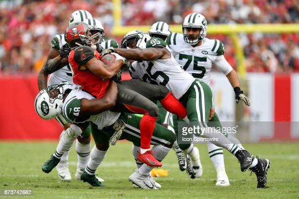 New York Jets linebacker Jordan Jenkins lifts Tampa Bay Buccaneers running back Doug Martin off the ground and slams him to the turf during the...